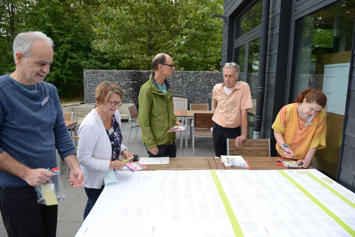 Bürgerinnen und Bürger diskutieren anhand einer großen Tabelle die Inhalte des WSP im Außenbereich während der Revier-Werkstatt