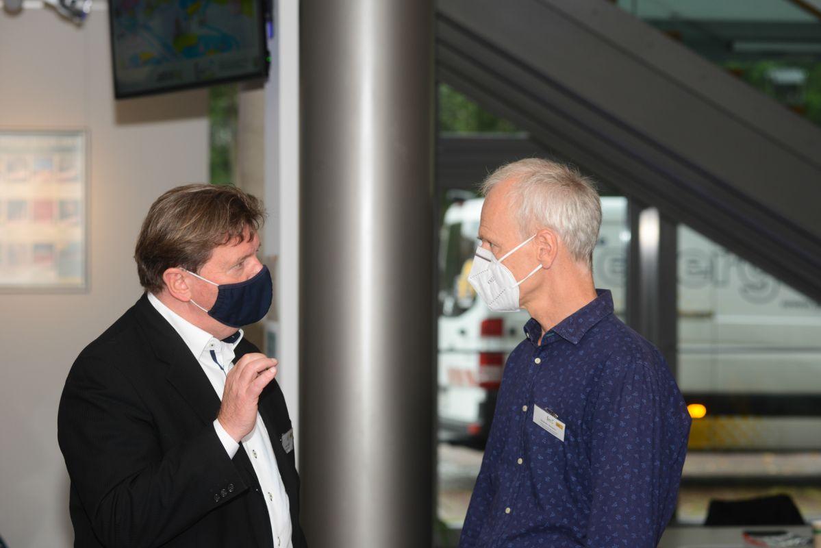 Zwei Männer mit Mund-Nasen-Bedeckung im Dialog