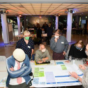 Menschen sitzen um eine große Tabelle an einem Tisch. Alle tragen eine Mund-Nasen-Bedeckung