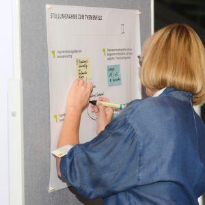 Eine Frau schreibt mit einem Marker an einer Pinnwand