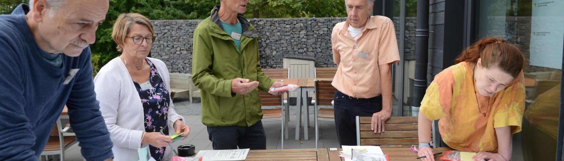 Menschen stehen um eine großformatige Tabelle auf einem Tisch im Außenbereich herum und bestücken diese mit bunten Klebezetteln