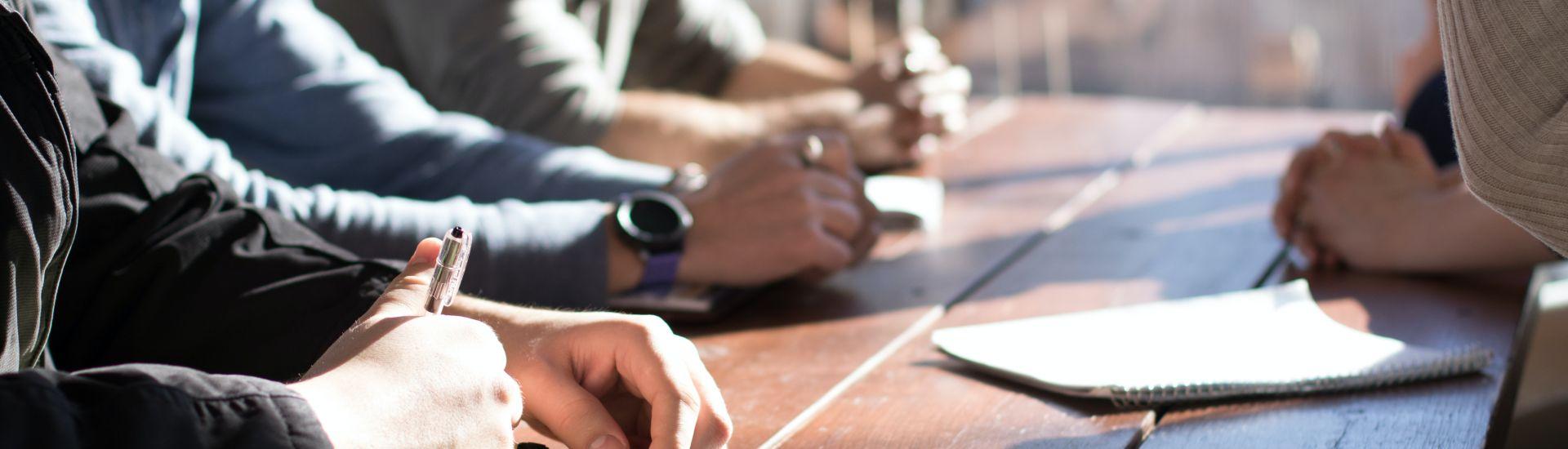 Menschen sitzen aneinem Tisch und machen sich Notizen.