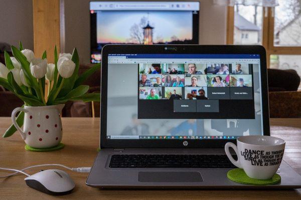 Laptop auf einem Tisch zeigt einer Webkonferenz