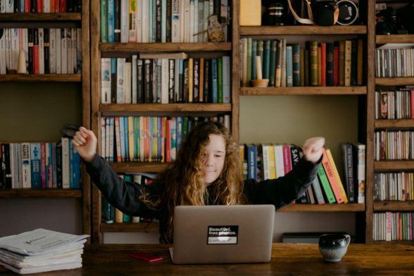Kind vor einem Bücherregal hinter einem Laptop