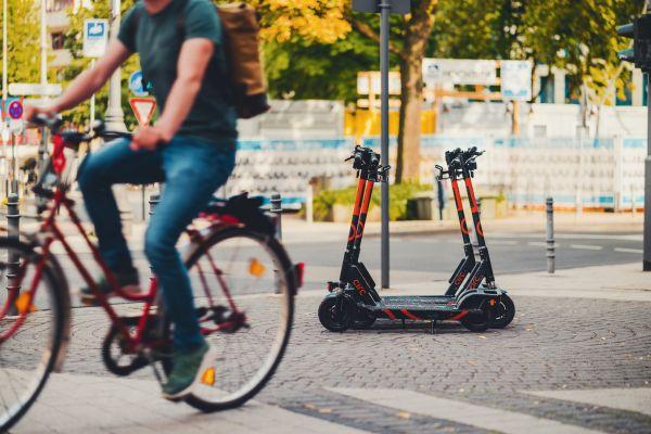 Mensch auf dem Fahrrad, E-Roller im Hintergrund