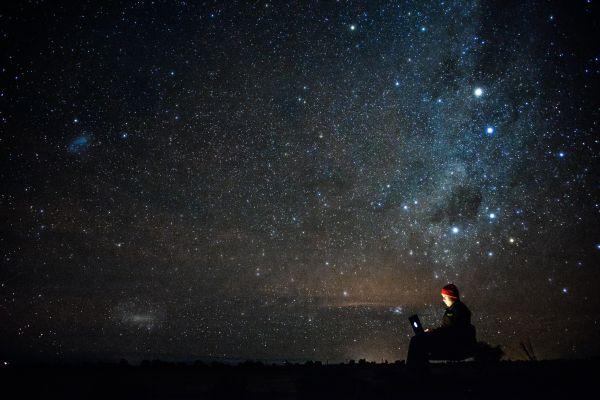 Mensch vor einem Sternenhimmel mit Laptop