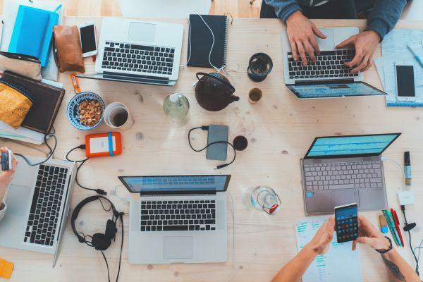 Laptops, Tassen und Bücher auf einem Tisch